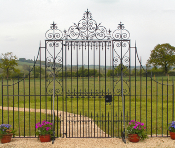 Kensington Entrance Gate. The design has been influenced by many old gates over the last 200 years to give a classical look. The side panels and overthrow include decorative scrollwork. Overall width 3.8m. Max. Ht. 2.8m. Railing at lowest 1.4 m high. Gate 1m wide x 2.2 m high. Decorative panel 0.4m wide. Railing panel 1m wide.