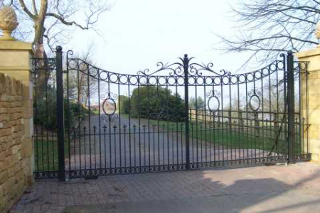 Dovers Driveway Gates. Decorative wrought iron scrollwork and finials with classical roundels. Downswept design. Matching side panels. Heavy quality wrought iron gates, galvanised and painted.