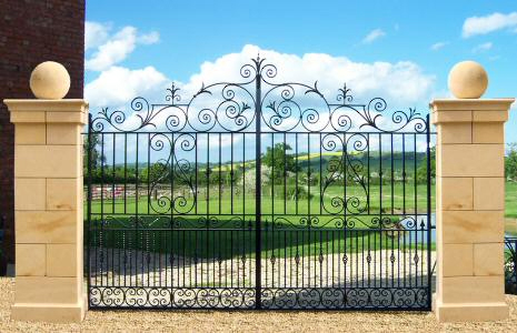 Chelsea Driveway Gates . This wrought iron gate design features handmade tightly rolled scrollwork, repousse, decorative collars and twisted bar with baskets. 12' (360cm) wide, 7' (210cm) high, 9' (270cm) at centre.