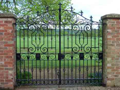 Tidmington Garden Gates. Decorative iron panels inset into the top half of the gate with decorative ironwork twisted bars and baskets interlaced at the bottom.