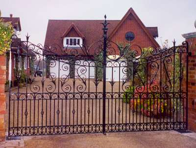Whichford Entrance Gates. Heavy quality wrought iron entrance gates. Large decorative 's' shaped wrought iron scrolls incorporating repousse.