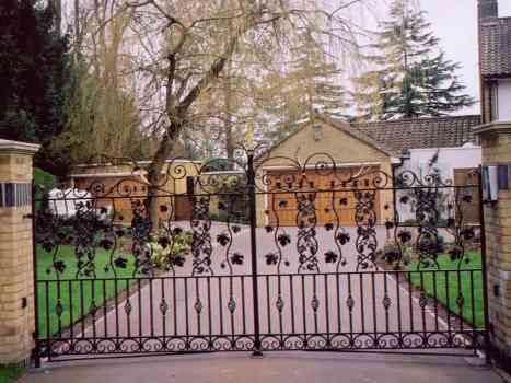 Wraysbury Driveway Gates. Cast iron foliage panels with grape vine leaves and fruits. Twisted bar and baskets with gilded collars and gilded leaves and rings incorporated into the top decoration.